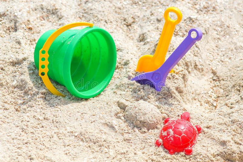 Children`s beach toys - buckets, spade and shovel on sand on a sunny day royalty free stock photography