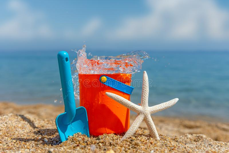 Children`s beach toys - buckets, spade and starfish on sand royalty free stock photos