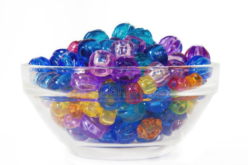 Pony Beads in a rainbow of colors on white in a glass bowl royalty free stock photography