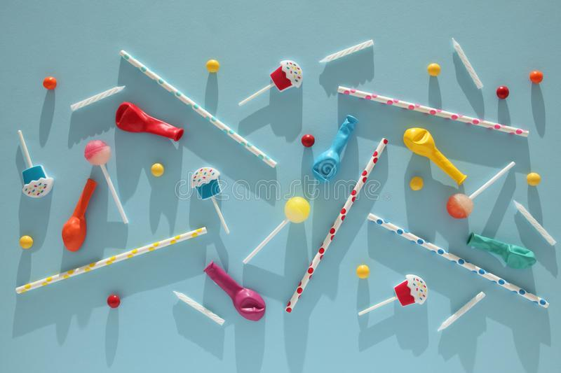 Children`s birthday blue background. Scattered colorful candies, balls, candles and straws royalty free stock photo