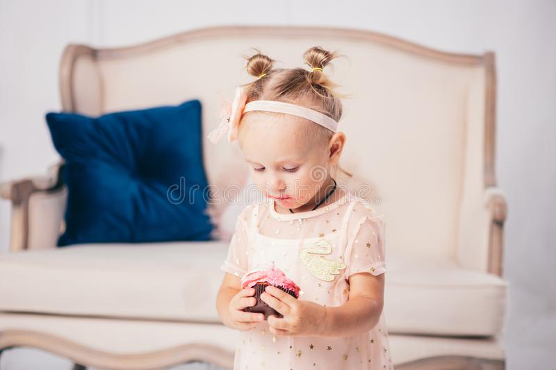 Children`s birthday. funny two-year-old Caucasian girl in pink dress standing to bedroom of house the background of couch and eat stock photo