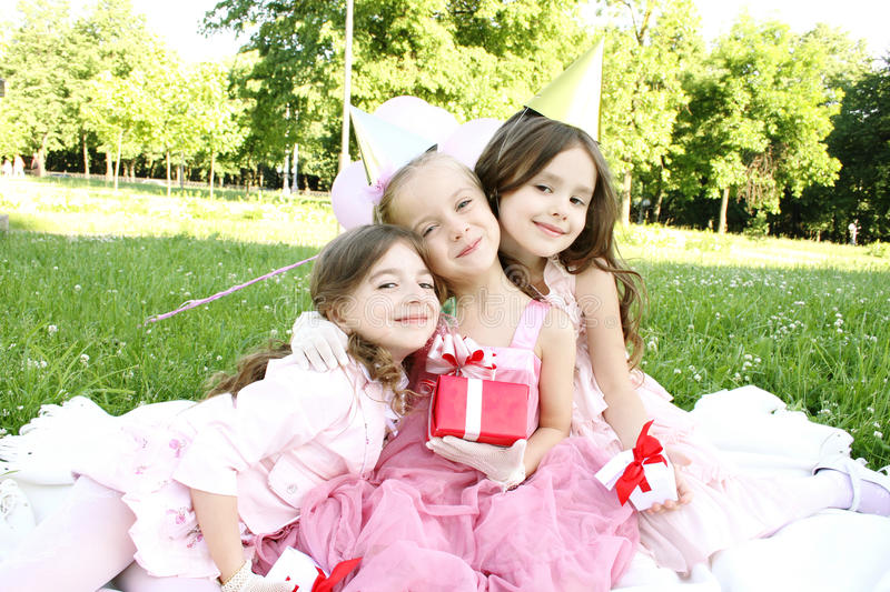 Children's Birthday Party outdoors. Three young girls outdoors merry, celebrate a birthday, give gifts royalty free stock photos