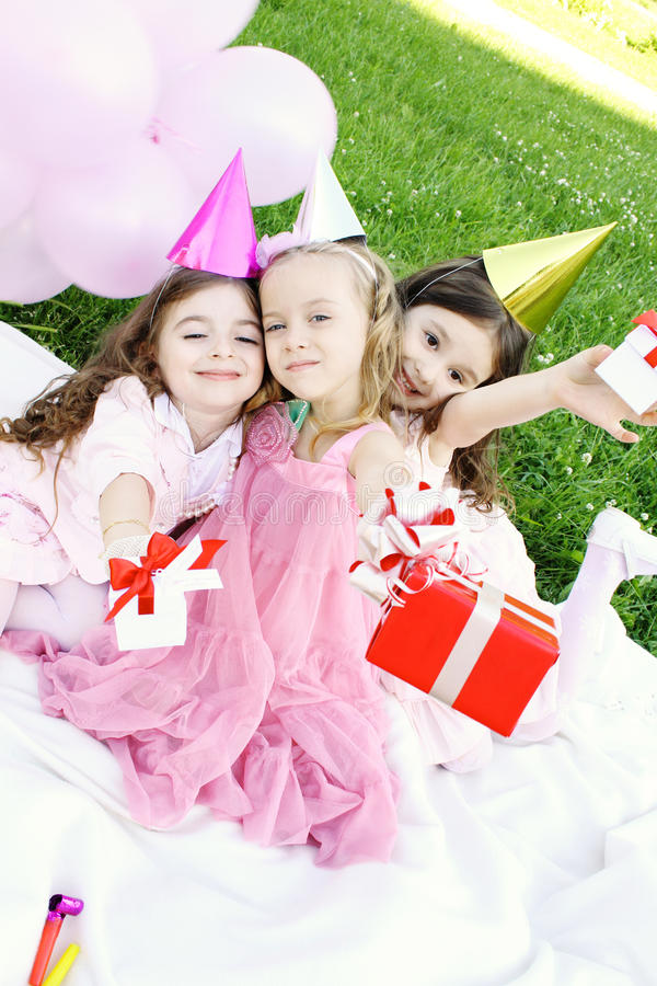 Children's Birthday Party outdoors. Three young girls outdoors merry, celebrate a birthday, give gifts stock photography