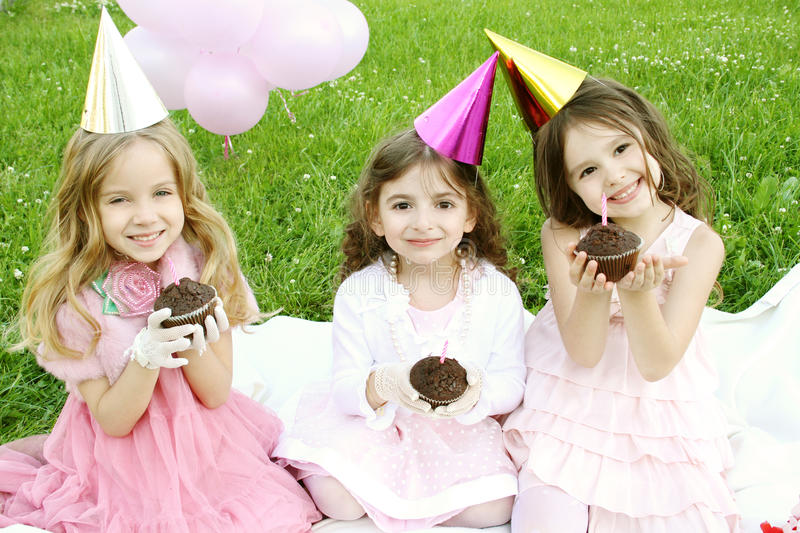 Children's Birthday Party outdoors. Three young girls outdoors merry, celebrate a birthday, give gifts stock images