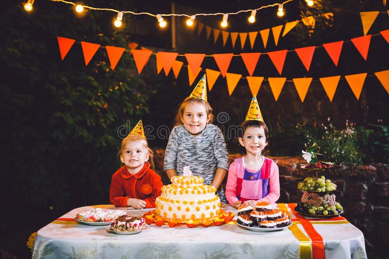 Children`s birthday party. Three cheerful children girls at the table eating cake with their hands and smearing their face. Fun a. Children`s birthday party royalty free stock photography