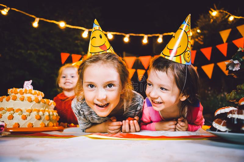Children`s birthday party. Three cheerful children girls at the table eating cake with their hands and smearing their face. Fun a. Children`s birthday party stock image