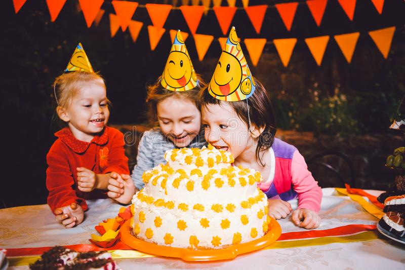 Children`s birthday party. Three cheerful children girls at the table eating cake with their hands and smearing their face. Fun a. Children`s birthday party stock photography
