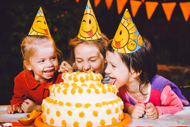 Children`s birthday party. Three cheerful children girls at the table eating cake with their hands and smearing their face. Fun a. Children`s birthday party royalty free stock photo