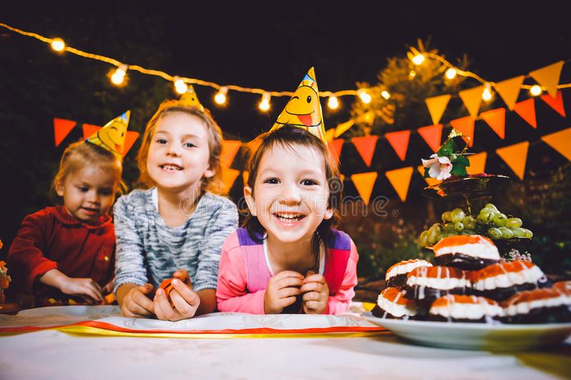 Children`s birthday party. Three cheerful children girls at the table eating cake with their hands and smearing their face. Fun a stock photography