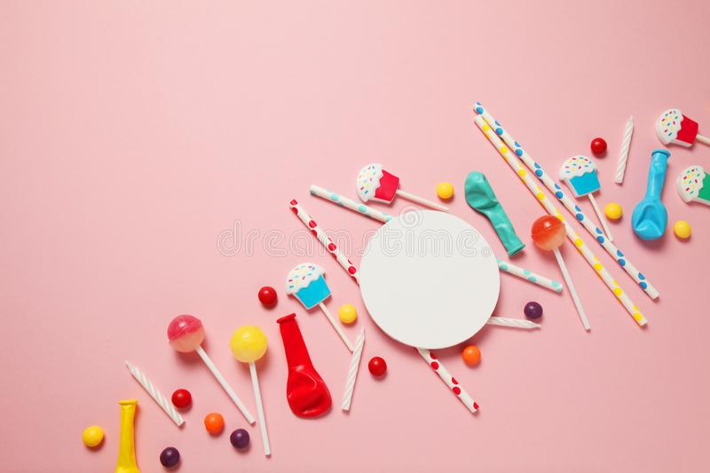 Children`s birthday pink background. Scattered colorful candies, balls, candles and straws royalty free stock photography