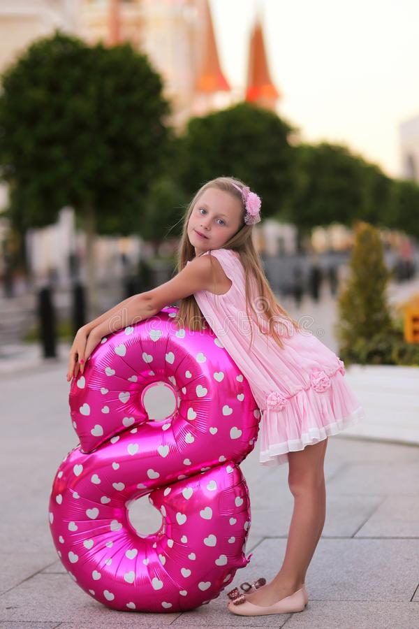 Children`s birthday. Smiling a beautiful blond little girl with a helium ball in the form of a figure eight celebrates her stock photos
