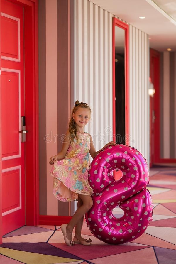 Children`s birthday. Smiling a beautiful blond little girl with a helium ball in the form of a figure eight celebrates her stock photo