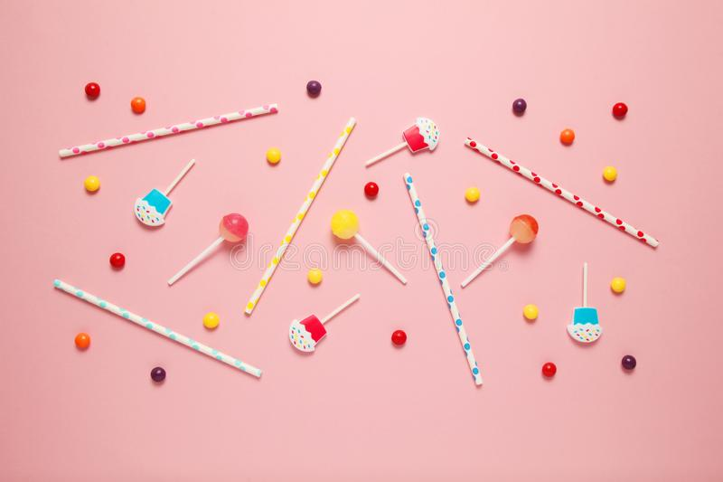 Children`s cheerful decor for a party, pink background. Sweet candies, bright balls, festive candles and straws royalty free stock image