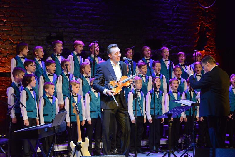 Children's choir and violinist onstage stock image