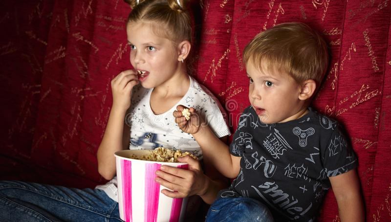 Children`s cinema: A girl and a boy watch a movie at home on a big red sofa in the dark and eat popcorn. royalty free stock photos