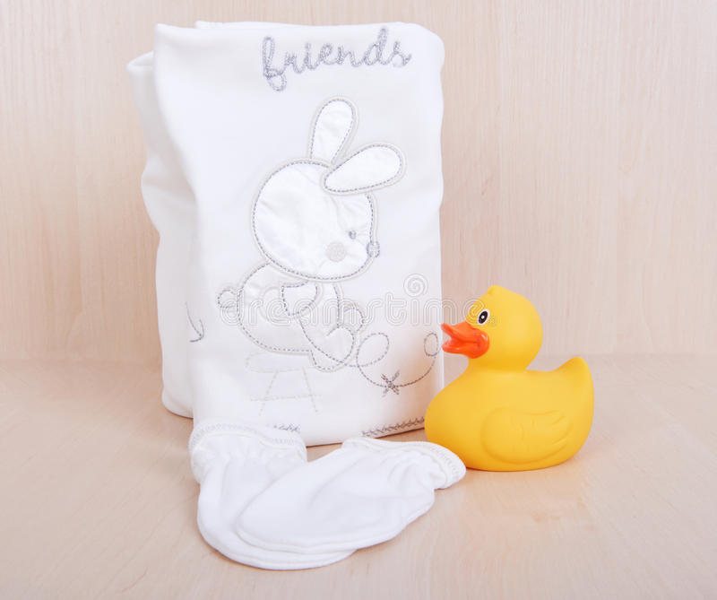 Children`s clothing diapers pajamas mittens socks vests sliders white background and ruber toy yellow duck royalty free stock photography