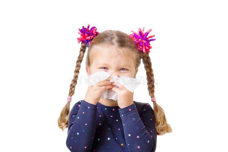 Children`s cold. The little girl has a runny nose. And blows her nose into paper handkerchief. Children`s cold, selective focus on a handkerchief. Acute royalty free stock photo