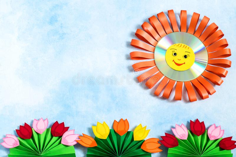 Children`s crafts made of paper and CD. Sun and flowers. Children`s crafts for spring and summer themes. Art project, DIY concept. Smiling sun from CD and paper royalty free stock photography