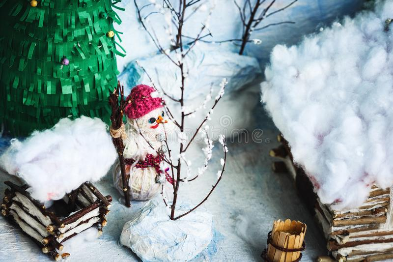 Children`s crafts of the winter yard in the snow: house, trees, well, snowman. Children`s crafts of the winter yard in the snow: house, trees, well, snowman stock photo