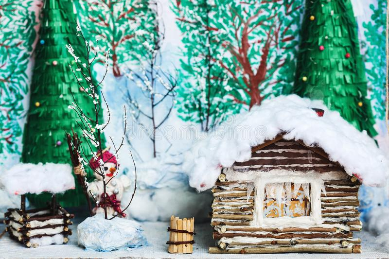 Children`s crafts of the winter yard in the snow: house, trees, well, snowman. Children`s crafts of the winter yard in the snow: house, trees, well, snowman royalty free stock photography
