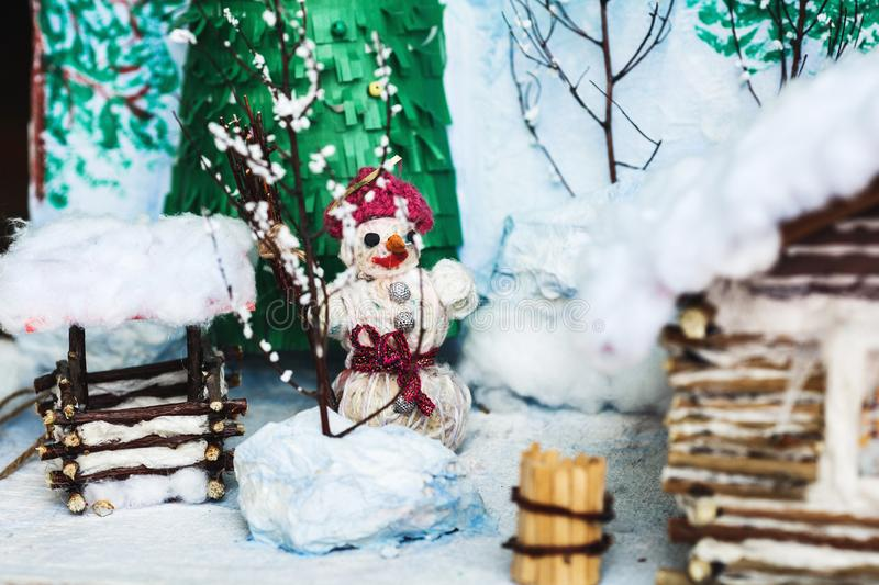Children`s crafts of the winter yard in the snow: house, trees, well, snowman. Children`s crafts of the winter yard in the snow: house, trees, well, snowman royalty free stock photo