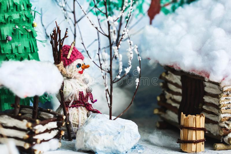 Children`s crafts of the winter yard in the snow: house, trees, well, snowman. Children`s crafts of the winter yard in the snow: house, trees, well, snowman stock image