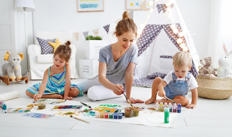 Children`s creativity. mother and children draw paints in play stock photos