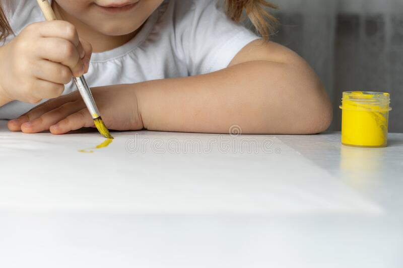 Children `s creativity in quarantine in connection with the coronavirus СOVID-19. Children hands draw with yellow paint on paper. children `s creativity in royalty free stock photo