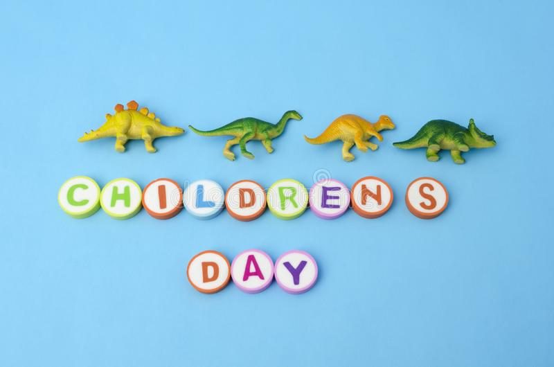 Children`s Day made from colorful letters and plastic dinosaur toys royalty free stock photo