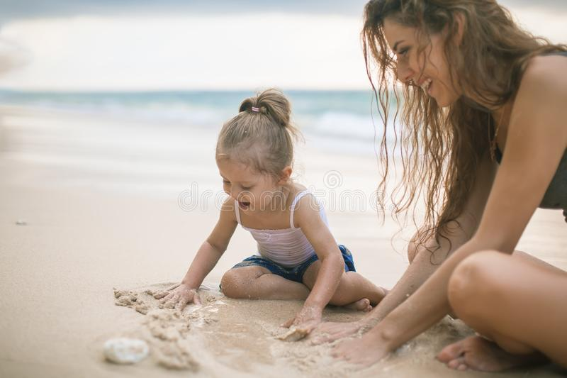 Children`s Day. Mom and baby playing near beach. royalty free stock images