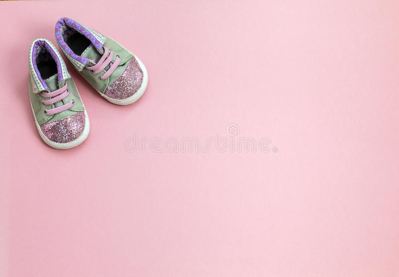 Children`s denim sports shoes for girls, stands on a pink background. stock image