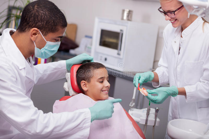 Children's dentist explains to the child how to properly wash th. Young boy at the dentist's office sit in the dentist's chair stock image
