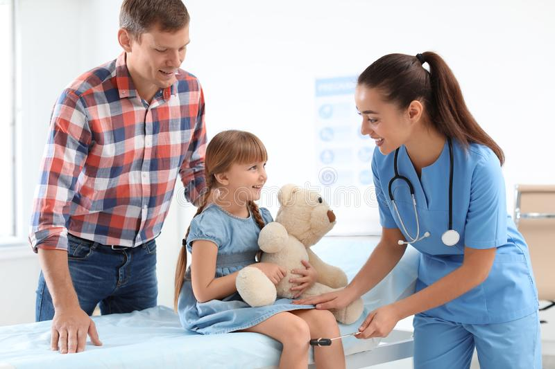Children`s doctor examining little girl near parent stock images