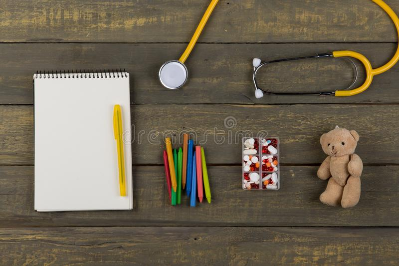 Children& x27;s doctor or pediatrician concept - blank notepad, pills, yellow stethoscope, Teddy bear toy, crayons royalty free stock image