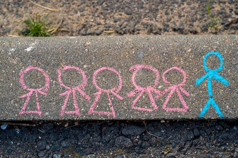 children's drawing with chalk on the asphalt, the concept of competition and the leader. Little men. one man and many women. royalty free stock photo