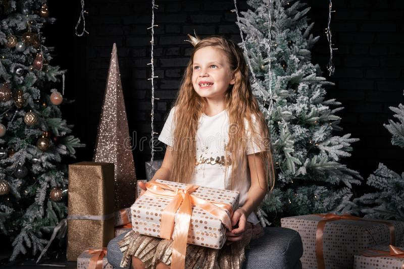 A girl sits on a chair and holds a box with a gift in her hands. Children`s dreams and anticipation: A girl sits on a chair and holds a box with a gift in her royalty free stock image
