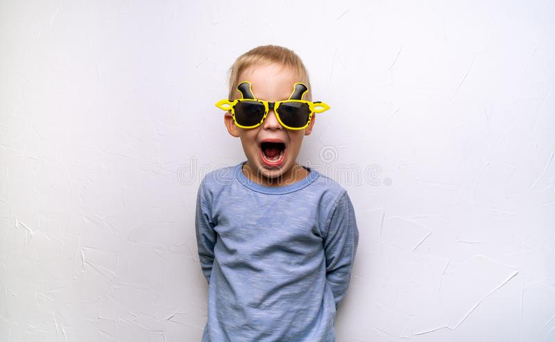 Children`s emotions and screaming: A little boy in funny yellow sunglasses screams against the white wall. Portrait stock image