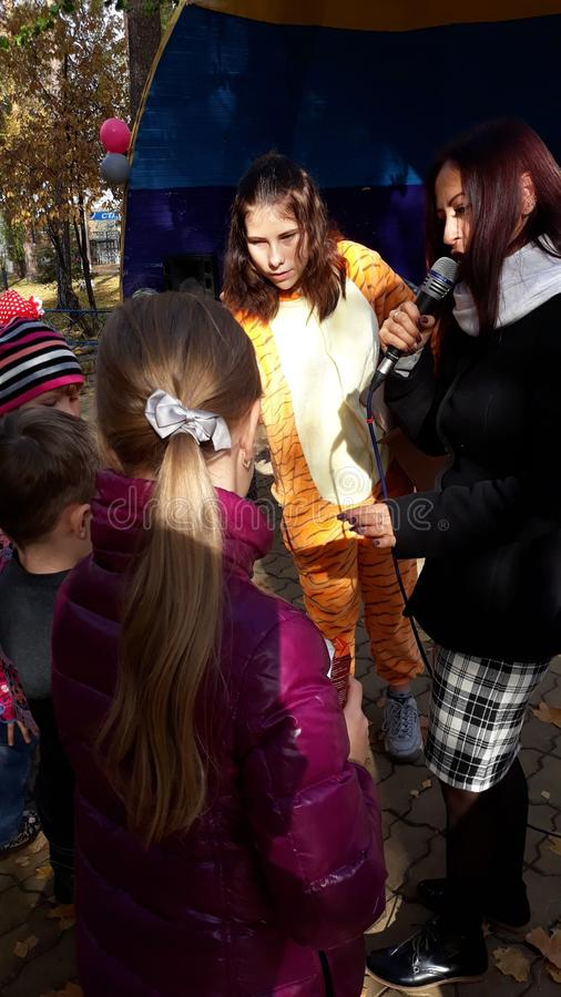 Children`s Entertainers Giraffe Gives Gifts. Presenter with Microphone. stock photography