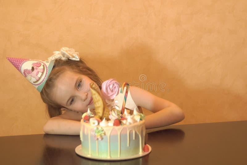 Children& x27; s-födelsedagparti Liten flicka som ser kakan Lyckligt födelsedagbegrepp arkivfoto