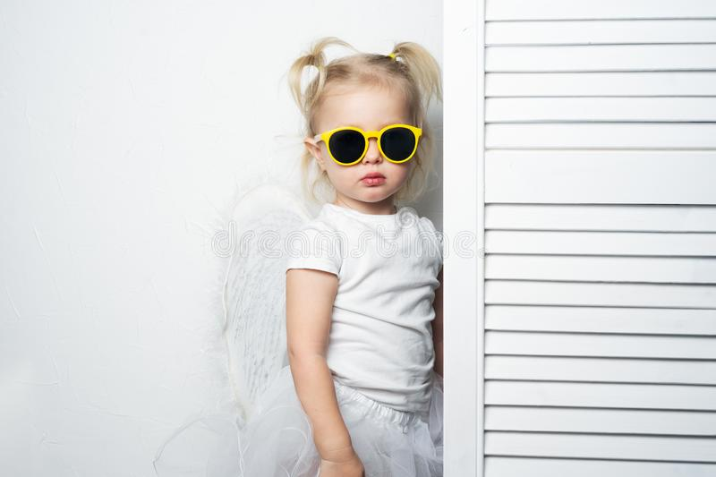 Children`s fashion: a little girl in yellow sunglasses is posing seriously against a white wall, imitating a top model. royalty free stock photography