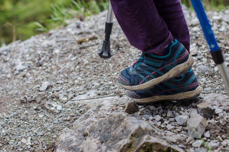 Child`s feet walk along the mountain path stock image