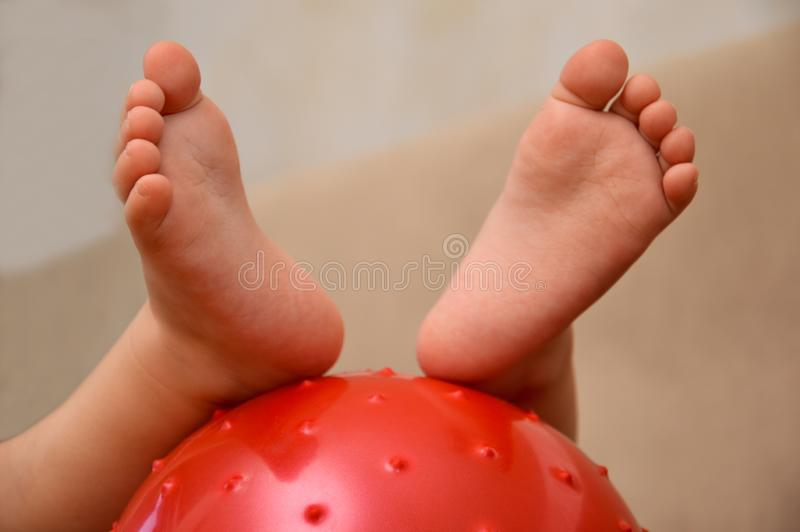 Children`s feet on the ball. Baby feet on the ball. Small baby feet stock photo