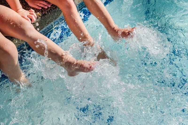 Children`s feet splashing in pool water stock photos