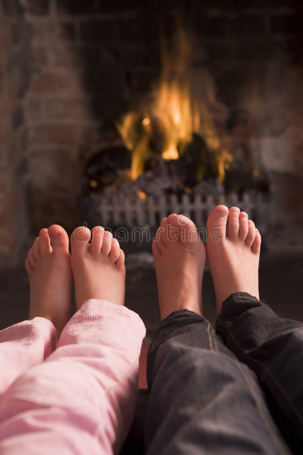 Children's feet warming at a fireplace stock image