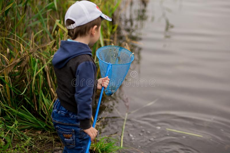 Children`s fishing net. A preschooler boy in a tracksuit and cap catches dirt and grass with a baby net. horizontal photo on a. Pond royalty free stock photography
