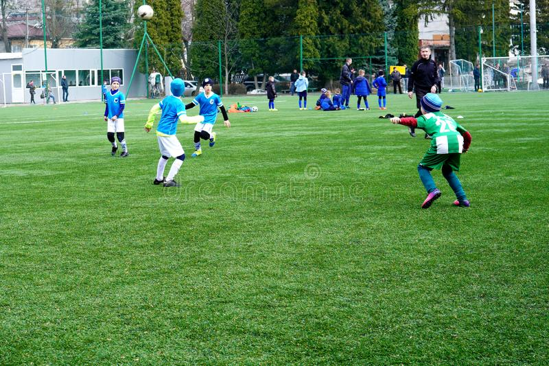 Children`s Football Team on the Pitch. Children`s football training ground. Young Soccer Players Running After the Ball. stock photos