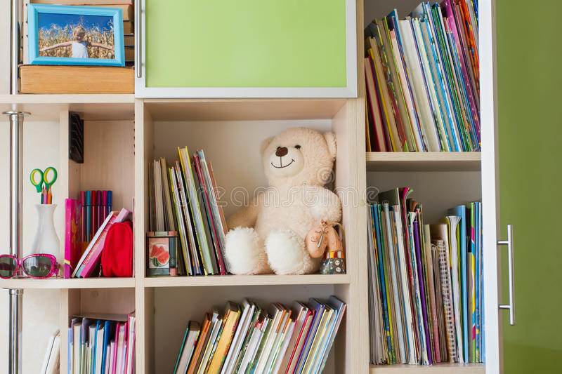 Children's furniture with bookshelves, books and teddy bear stock images