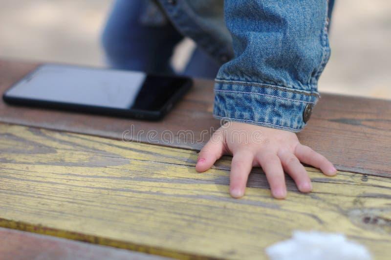Children& x27; s gömma i handflatan ligger på tabellen bredvid telefonen royaltyfri fotografi