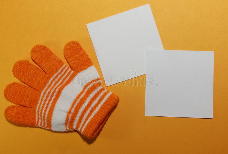 Children`s glove, on the child`s hand, orange striped lies on a yellow surface with two white square shaped blank sheets for writi. Ng text stock images