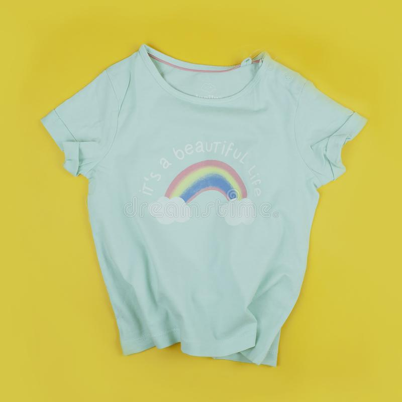 Children`s green T-shirt on a yellow background with a rainbow pattern and a life-affirming text `it`s a beautiful life` royalty free stock photos